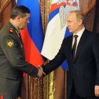 Arctic front: Russian President Vladimir Putin shakes hands with Chief of the General Staff of the Russian Armed Forces Col. Gen. Valery Gerasimov during a meeting with the top military brass in Moscow on Tuesday. | AP