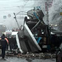 Aftermath: Russian firefighters and security personnel inspect a trolleybus destroyed by a bomb in Volgograd on Monday. Ten people were killed by the blast, the second attack in the city in two days. | AFP-JIJI