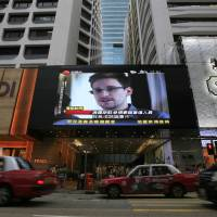 Secret sharer: A TV screen at a Hong Kong shopping mall shows a news report of Edward Snowden on June 23. The former National Security Agency contractor may have stolen 20,000 classified Australian intelligence files, a report said Thursday. | AP