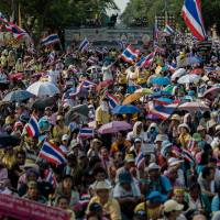 Mass message: Demonstrators gather outside the Government House in Bangkok on Monday. Thailand's premier, Yingluck Shinawatra, called a snap election the same day to try to defuse the kingdom's political crisis, but protesters kept up their fight to topple the government. | AFP-JIJI