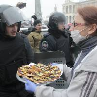 Food for thought: A pro-European Union activist tries to give food to riot police officers preparing to block the Independence Square in Kiev on Monday. Organizers called on protesters to vacate City Hall and another building the opposition had used as its headquarters. | AP