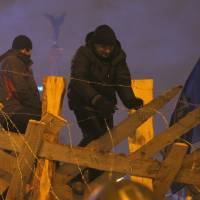 Manning the barricades: Pro-European Union activists reinforce the fence around their tent camp in Independence Square in Kiev on Wednesday. | AP
