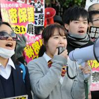 A girl uses a loudspeaker to criticize the state secrets bill Friday near the Diet, where the government-sponsored legislation was poised to sail through the Upper House.  | SATOKO KAWASAKI
