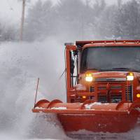 Highway crews work to clear snow from roads on Thursday in Henniker, New Hampshire.  | AP
