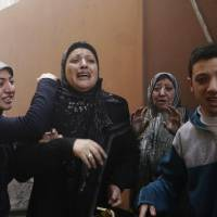 Lebanese family members who evacuated their damaged home cry out following an explosion in a southern suburb of Beirut, Lebanon. | AP