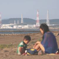 Restarting in the summer?: Tepco's Kashiwazaki-Kariwa nuclear plant is seen from a beach in Kashiwazaki city, Niigata Prefecture, in September. | BLOOMBERG