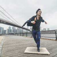 Steppin' out: Sendai native Kazunori Kumagai practices his tap-dance skills beside the Brooklyn Bridge in New York, the city that he now calls home. | © MAKOTO EBI