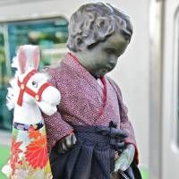 Mind the gap: Hamamatsucho Station's cute mascot, a replica of Brussels' Mannekin Pis, pensively holds his own on the platform. | KIT NAGAMURA