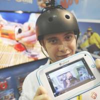 Toy story: At a London toy fair, Alexandra Delage from Lexibook holds a tablet connected wirelessly to a mini camera that is attached to his helmet. | AFP-JIJI