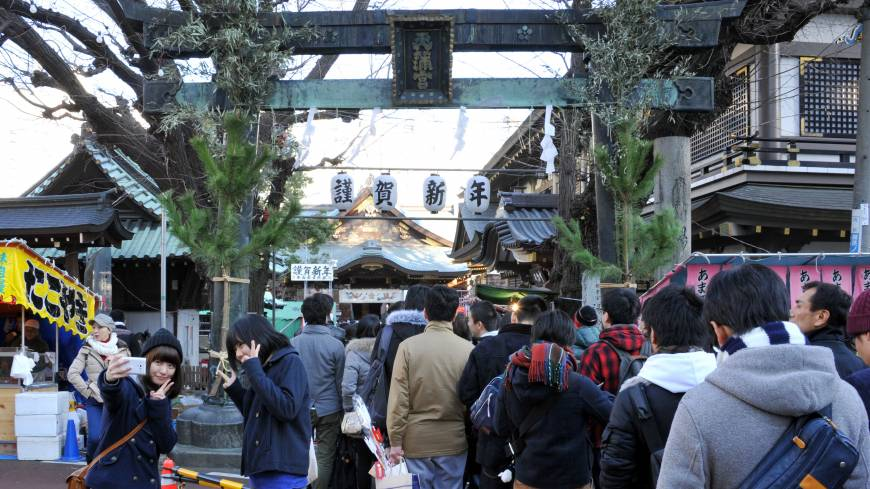 A long line of visitors snakes out of Yushima Tenjin Shrine on the first morning of 2014.