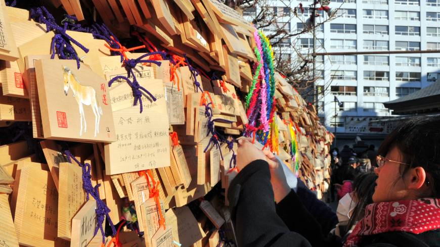 'Ema' (traditional Shinto plaques) displaying the hand-written messages and wishes of visitors are hung outside Yushima Tenjin Shrine in Tokyo's Bunkyo Ward. In the Chinese zodiac, 2014 is a year associated with the horse.