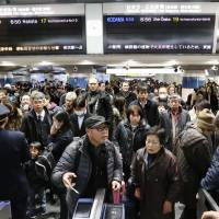 Anxious travelers wait outside tickets gates in Tokyo Station Friday morning after a major fire near Yurakucho Station halted train service for the Tokaido Shinkansen and other major train lines in Tokyo.  | KYODO
