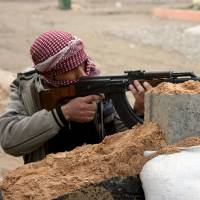 Enemy in sight: A gunman aims his rifle during clashes with Iraqi security forces in Fallujah Jan. 5.   AP
