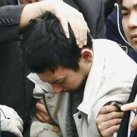 Yuta Sugimoto is taken by police officers to the Kawasaki branch of the Yokohama District Prosecutor's Office on Thursday after he was arrested in Yokohama. | KYODO