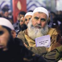 Disinterested parties?: An Egyptian Salafi holds a copy of the new constitution during a lecture entitled 'Know Your Constitution' in El-Saf, south of Cairo, on Thursday. | AP