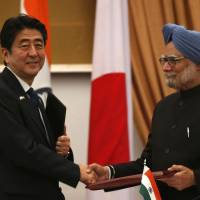 HeadlineKey partners: Prime Minister Shinzo Abe and Indian Prime Minister Manmohan Singh shake hands as they exchange signed agreements during a meeting in New Delhi on Saturday. | AP