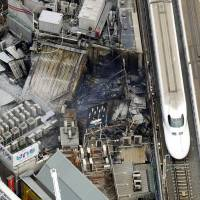 Blazing by: A JR Tokai bullet train plies a stretch of track near JR Yurakucho Station at 12:22 p.m. after a blaze that affected several buildings along the route was doused. | KYODO