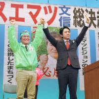 Vote for me!: Bunshin Suematsu (left), who is running in the Nago mayoral race, greets supporters Thursday. | KYODO
