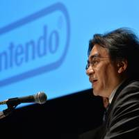 Nintendo Co. president Satoru Iwata speaks about the company's business strategy in Tokyo on Thursday.  Iwata will slash his salary in half after announcing a 30 percent dive in nine-month profit on weak demand for its new Wii U video game console as gamers are enticed by cheap, downloadable games for mobiles. | AFP-JIJI
