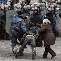Earthly power: A woman hits a riot police officer with a cross as he drags a protester away during clashes in the Ukrainian capital of Kiev on Wednesday. | AFP-JIJI
