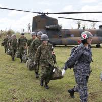 Emergency landing: A Self-Defense Forces medical team arrives aboard a Chinook chopper on Cebu Island in the Philippines to assist victims of Typhoon Haiyan on Nov. 24. | KYODO