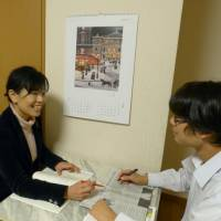 Home working: Midoriko Takahara discusses an English newspaper article with her son Reo. Takahara, who also runs a cram school in Tokyo, says she personally takes charge of her children's English education. | AKIHITO TAKAHARA