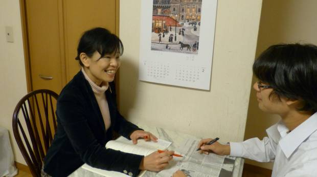 Home working: Midoriko Takahara discusses an English newspaper article with her son Reo. Takahara, who also runs a cram school in Tokyo, says she personally takes charge of her children's English education.