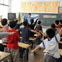 Get active: An assistant language teacher (ALT) joins an English lesson at Koyamadai Elementary School in Tokyo. | YOSHIAKI MIURA
