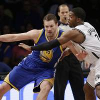 Net gain: Golden State's David Lee (left) tries to find a way past Brooklyn's Joe Johnson during the Nets' 102-98 win on Wednesday. | AP