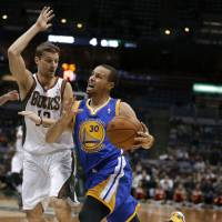 Streak continues: Golden State's Stephen Curry drives on Milwaukee's Luke Ridnour in the first half on Tuesday night. The Warriors beat the Bucks 101-80. | AP