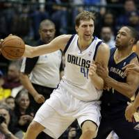 Vintage outing: Dallas' Dirk Nowitzki backs down New Orleans' Eric Gordon in the second half on Saturday night. The Mavericks beat the Pelicans 110-107. | AP