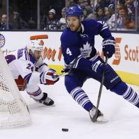Around the corner: Toronto's Cody Franson skates away from New York's Ryan Callahan in the first period on Saturday night. | AP