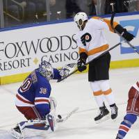 None shall pass: New York goalie Henrik Lundqvist blocks a shot as Philadelphia's Wayne Simmonds watches on Sunday. | AP