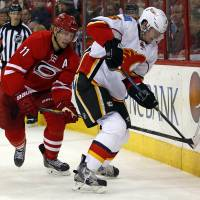 Board work: Carolina's Jordan Staal (left) vies for the puck with Calgary's Ladislav Smid in the second period on Monday night. The Flames blanked the Hurricanes 2-0. | AP