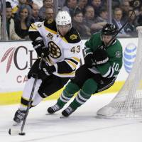 On his heels: Boston's Matt Bartkowski clears the puck ahead of Dallas' Shawn Horcoff in the first period on Thursday. The Bruins defeated the Stars 4-2. | AP