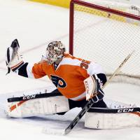 In the glove: Philadelphia's Steve Mason makes a save against Detroit in the third period on Tuesday night. The Flyers won 5-0. | AP