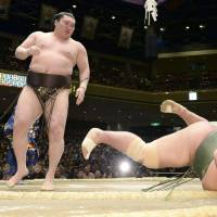 Triumphant stand: Hakuho watches Toyonoshima falls after a forceful shove on Monday at Ryogoku Kokugikan. | KYODO