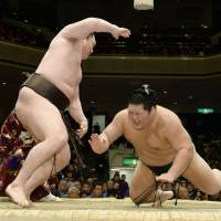 Winning formula: Yokozuna Hakuho's brute strength carries him past No.2 maegashira Chiyotairyu on Wednesday at Ryogoku Kokugikan. Hakuho improved to 4-0 at the New Year Grand Sumo Tournament. | KYODO