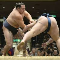 Staying in the hunt: Kakuryu (left) improves to 9-1 at the New Year Grand Sumo Tournament, going on the offensive against Goeido on Tuesday at Ryogoku Kokugikan. | KYODO