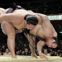 Muscular triumph: Endo overpowers Kotooshu on Friday at the New Year Grand Sumo Tournament, improving to 10-3.   | KYODO