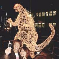 A couple pose for a photograph in front of a Godzilla Christmas illumination display in Shinjuku in November 2002. | KYODO