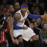 Imposing their will: New York's Carmelo Anthony backs down Miami's Dwyane Wade in the second half on Thursday night. | AP