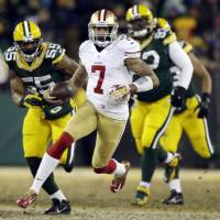Striking gold: 49ers quarterback Colin Kaepernick runs away from Packers defenders during their NFC wild-card game on Sunday in Green Bay, Wisconsin. San Francisco won 23-20. | AP