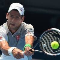 Expeditious victory: Novak Djokovic plays a shot from Leonardo Mayer in their second-round match at the Australian Open on Wednesday. Djokovic won 6-0, 6-4, 6-4. | AFP-JIJI