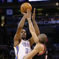 On fire: Oklahoma City's Kevin Durant puts up a jumper over Portland's Nicolas Batum in the fourth quarter on Tuesday night. The Thunder beat the Blazers 105-97. | AP