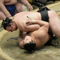 Pinned down: Kotooshu lays on top of Okinoumi after beating him at the New Year Grand Sumo Tournament on Monday. | KYODO