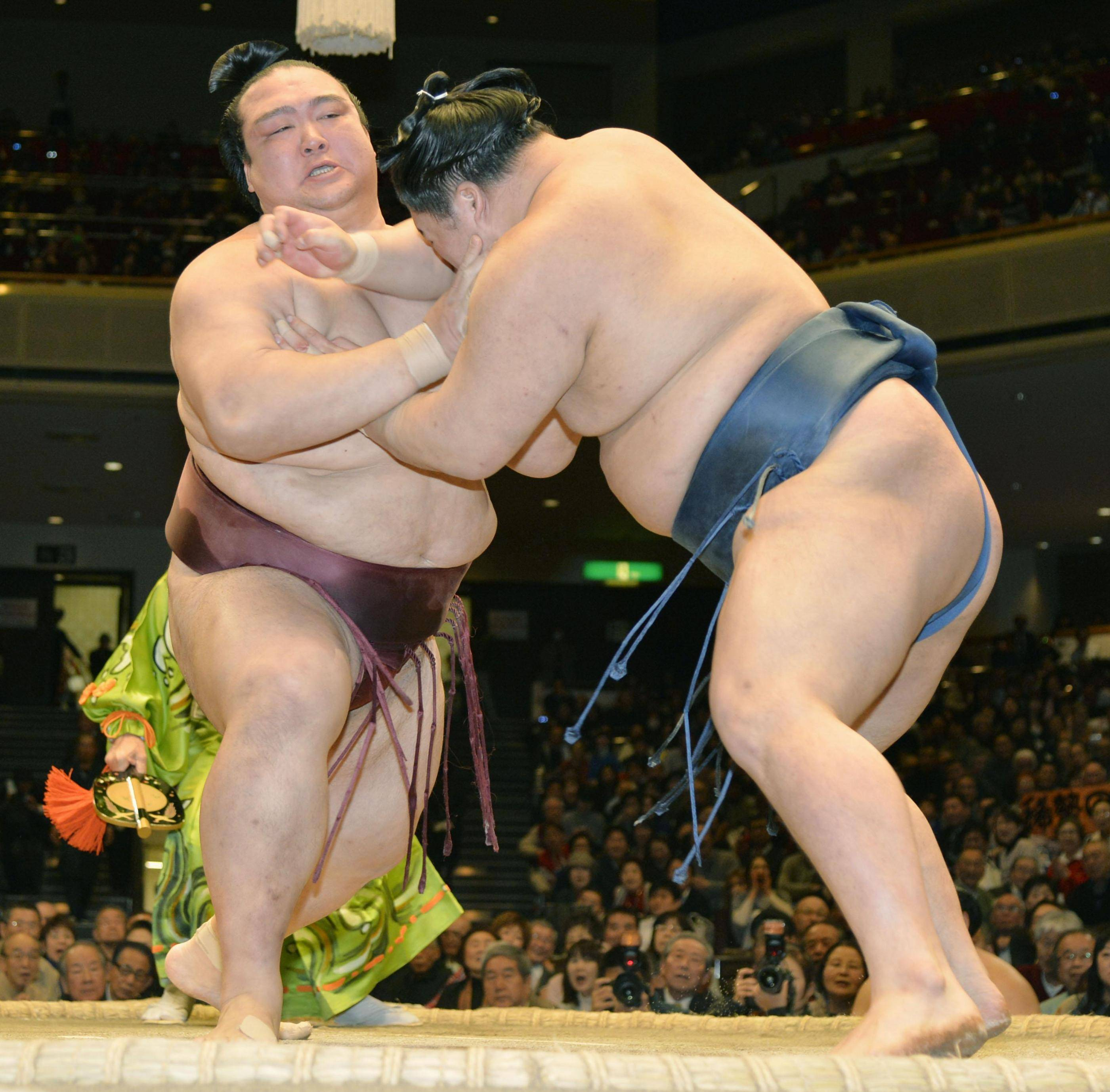 Strength on display: Ozeki Kisenosato (left) forces Goeido out of the raised ring on Wednesday at the New Year Grand Sumo Tournament. | KYODO
