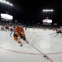 Take me out to the hockey game: Ducks winger Daniel Winnik controls the puck during the first period of Anaheim's game against the Kings on Saturday at Dodger Stadium. The Ducks won 3-0 in the first NHL contest to be held at the Los Angeles ballpark. | AP