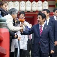 Back to base: Prime Minister Shinzo Abe greets fellow residents in his hometown of Shimonoseki, Yamaguchi Prefecture, on Sunday. | KYODO