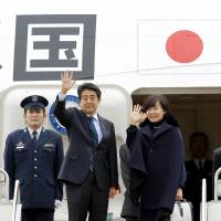 Commercial diplomacy: Prime Minister Shinzo Abe and his wife, Akie, board a government jet Thursday at Haneda airport in Tokyo at the start of a tour of Middle East and African nations. | KYODO